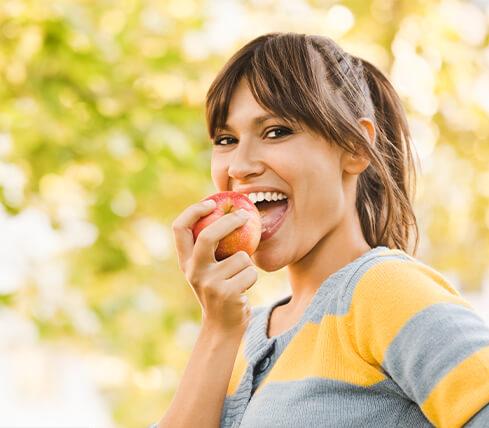 woman outside eating an apple