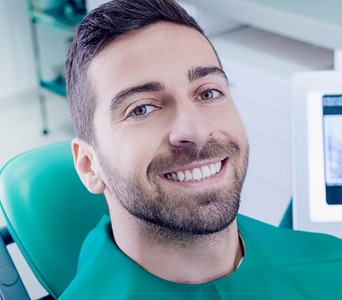 man in a dental chair smiling