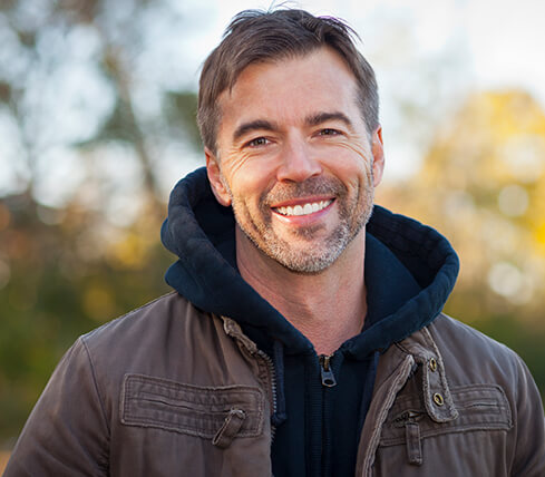 man in a gray jacket standing outside smiling